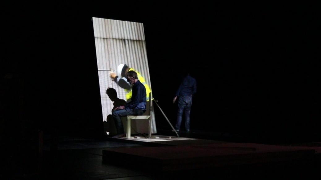 un danseur assis devant la projection vidéo d'un ouvier