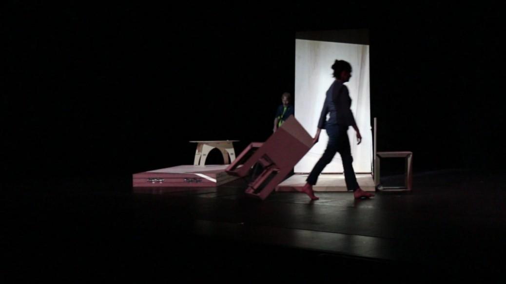 une danseuse tire une chaise sur le sol