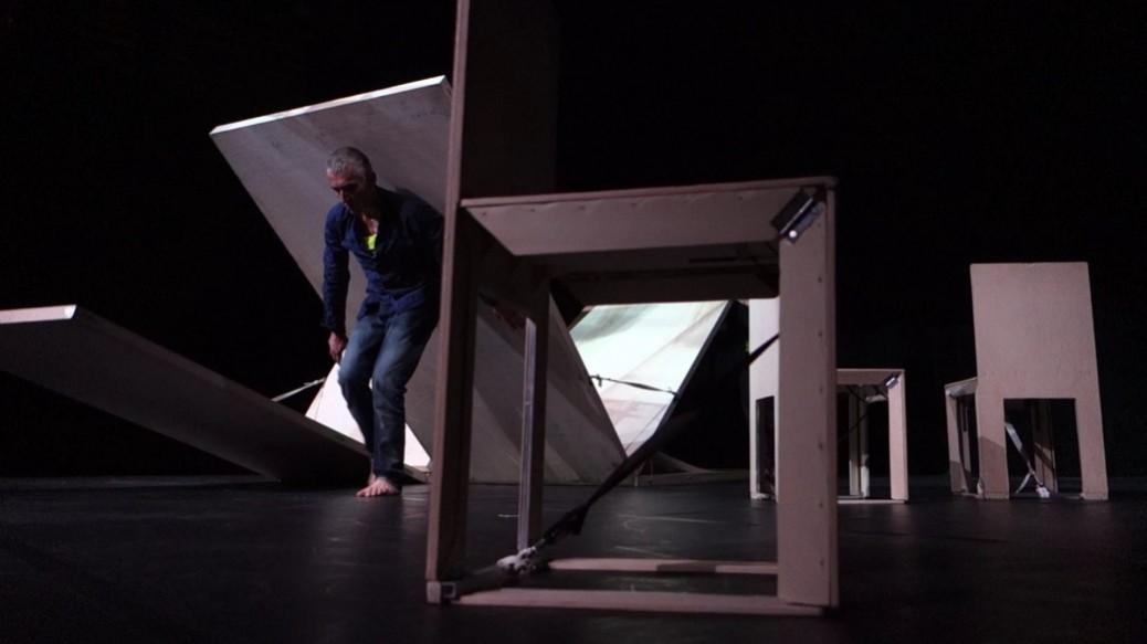 un danseur porte un panneau de bois