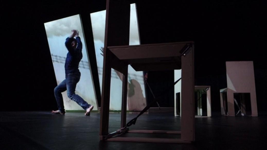 Pieds de chaise au premier plan et danseur au fond