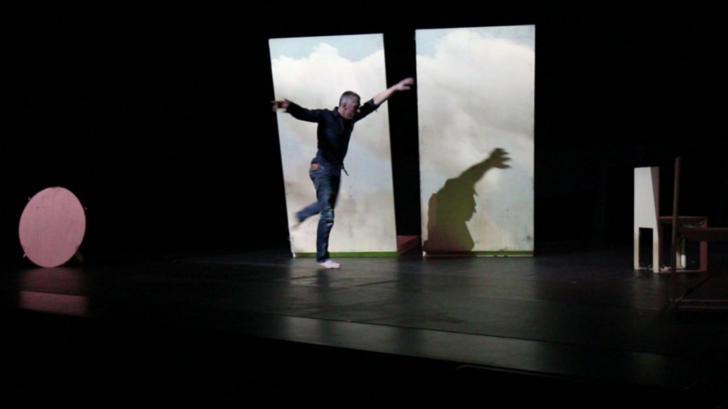 Danseur devant deux panneaux de bois, où sont projetés des nuages
